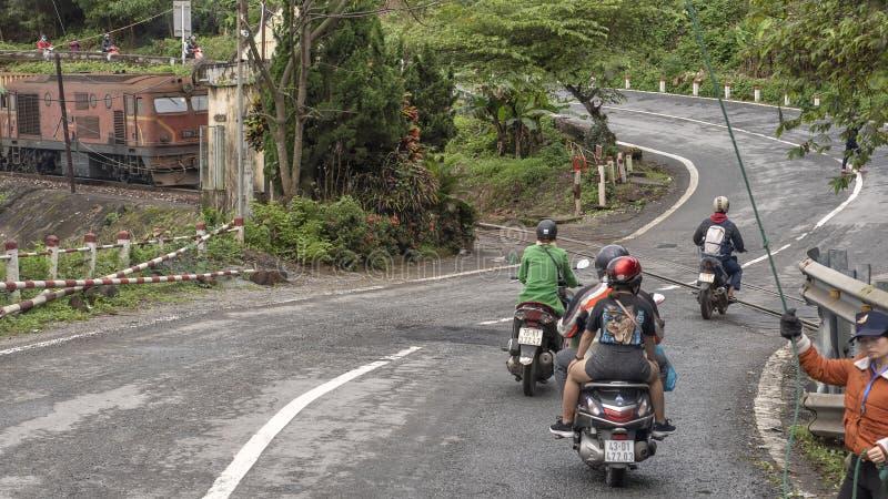 Motocicletas con los pasajeros que recomienzan después de parar para que el tren pase, Hai Van Pass, Vietnam fotos de archivo libres de regalías