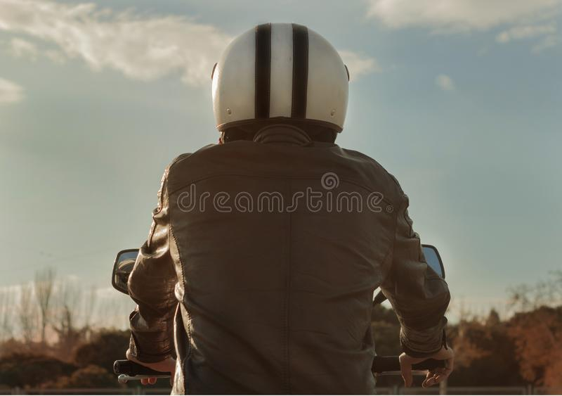 Motocicletta di guida dell'uomo con il bomber ed il casco marroni fotografia stock