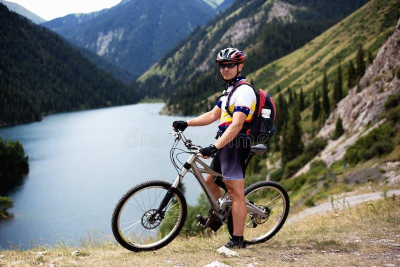 Motociclista al lato del lago della montagna immagine stock