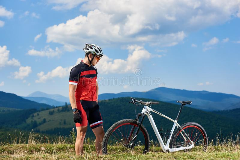 Motociclista atlético novo do desportista no sportswear profissional que olha o mtb no monte gramíneo da montanha imagens de stock