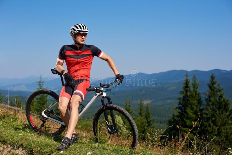 Motociclista atlético novo do turista que descansa em sua bicicleta no monte da montanha imagens de stock