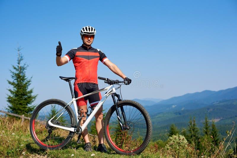 Motociclista bem sucedido atlético novo do turista no sportswear que está na bicicleta com gesto do polegar-acima imagem de stock royalty free