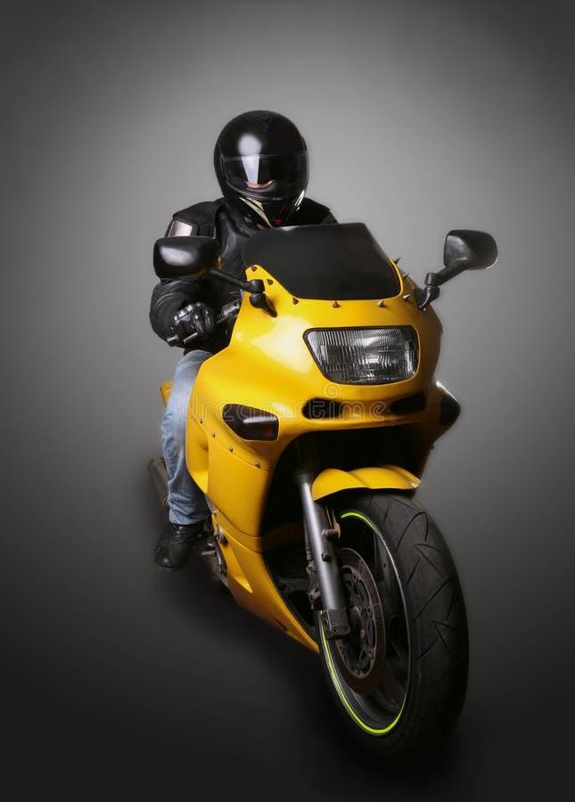 Motociclista in casco sul motociclo giallo fotografia stock libera da diritti