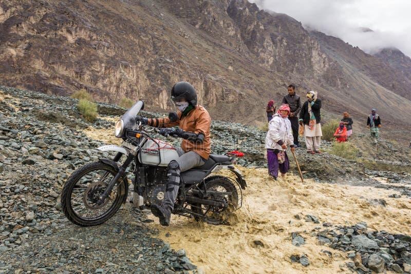 Motociclista che attraversa il fiume che entra dal ghiacciaio di fusione nelle montagne dell'Himalaya, regione di Ladakh, India fotografia stock