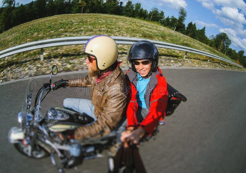 Motociclista che guida il suo motociclo sulla strada con il passeggero immagine stock libera da diritti