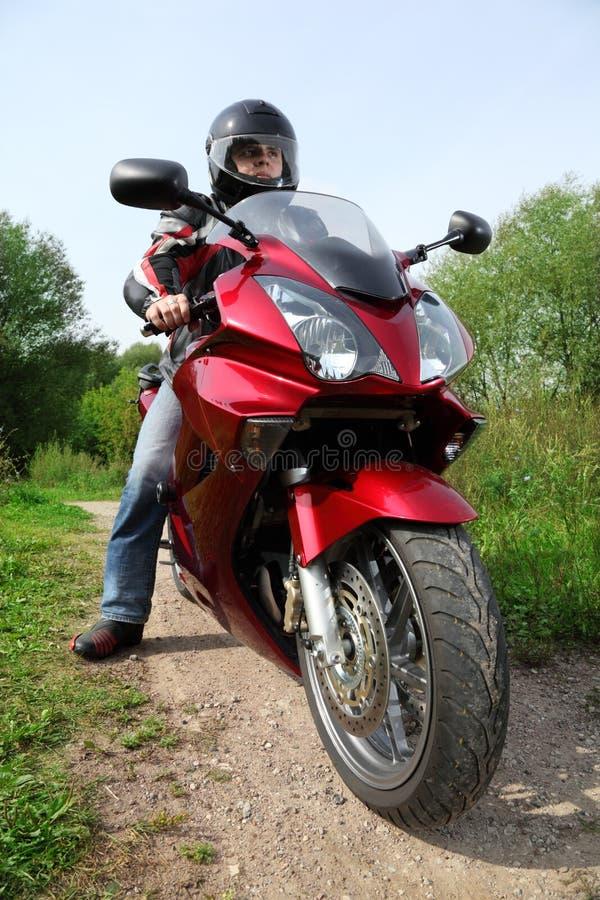 Motociclista che si leva in piedi sulla strada campestre fotografia stock