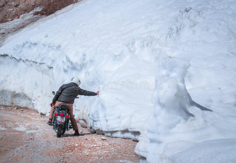 motociclista che tocca guida della neve sulle precipitazioni nevose enormi delle strade pericolose della montagna fotografia stock