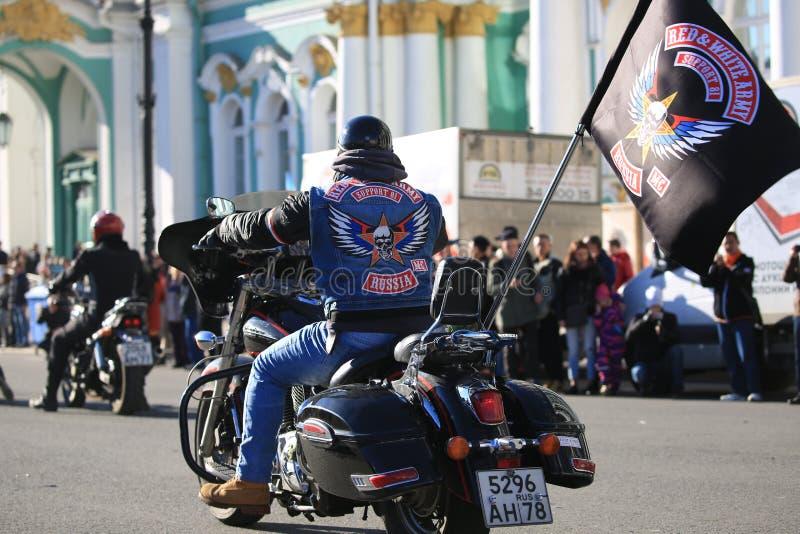 Motociclista con la bandiera del supporto rosso e bianco 81 del club del motociclo dell'esercito sulla sua bici immagini stock