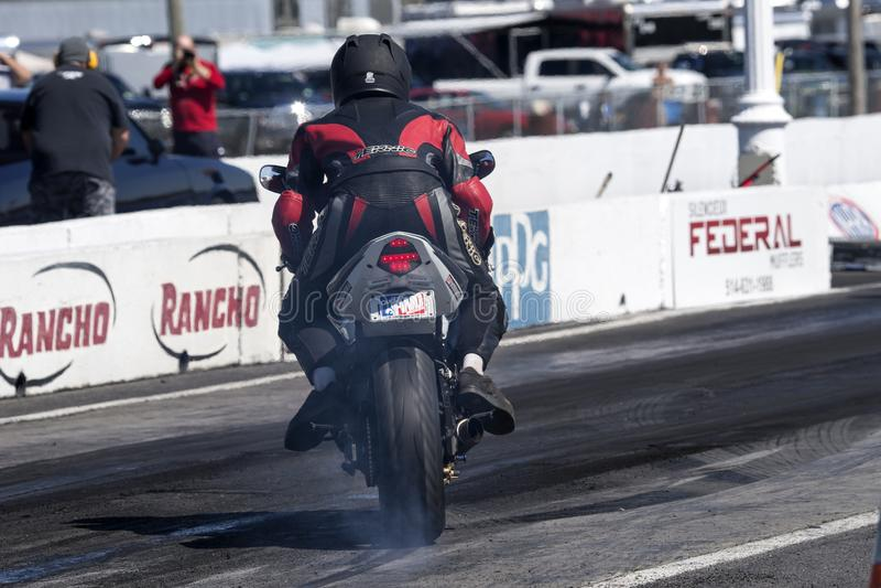 Motociclista con la motocicletta di sport che fa un burnout sulla pista fotografie stock libere da diritti