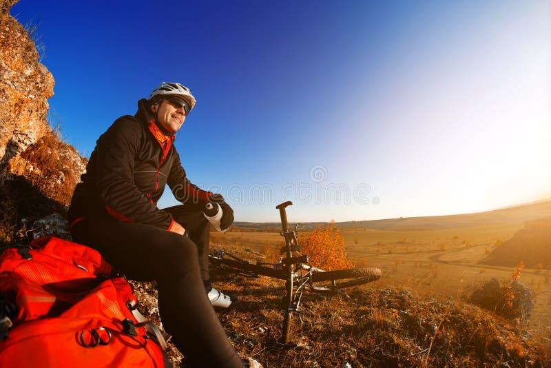 Motociclista da montanha que olha a vista na fuga da bicicleta na paisagem da mola Cavaleiro masculino que descansa na viagem do  foto de stock royalty free