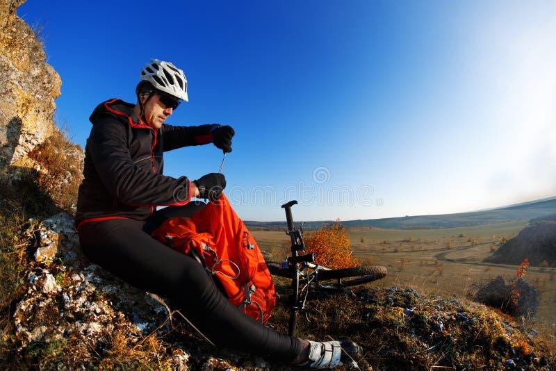 Motociclista da montanha que olha a vista na fuga da bicicleta na paisagem da mola Cavaleiro masculino que descansa na viagem do  fotos de stock
