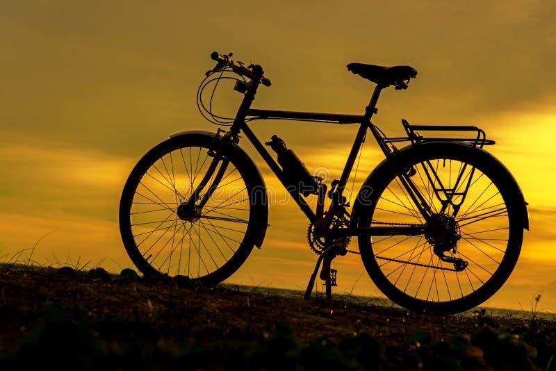 Motociclista da silhueta no por do sol sobre a praia fotos de stock royalty free