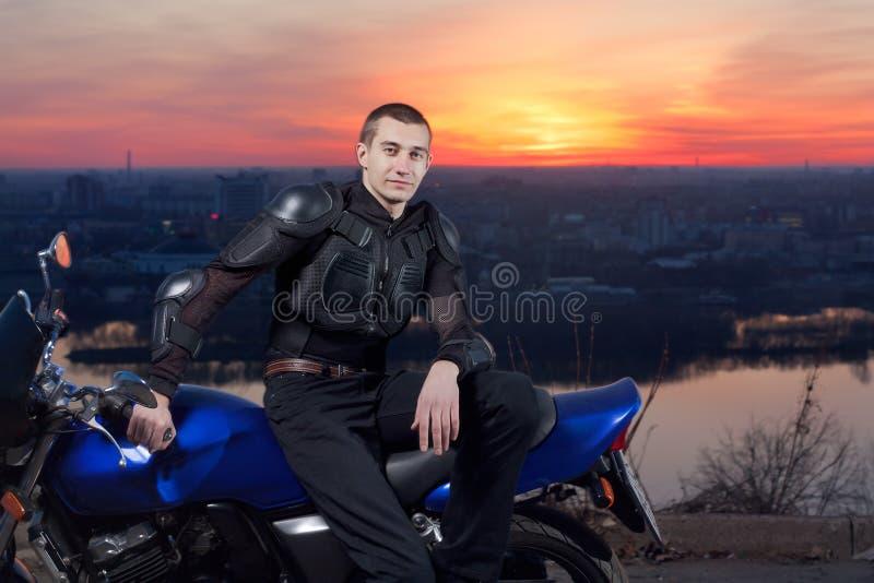 Motociclista de encontro a uma cidade da noite imagem de stock