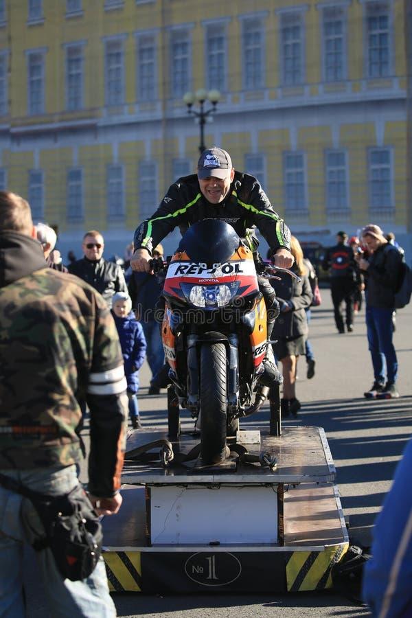 Motociclista de riso sem um capacete em um suporte de formação fotografia de stock
