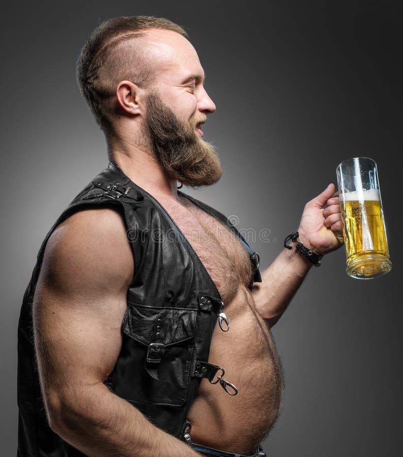 Motociclista de sorriso com barriga de cerveja O homem bebe a cerveja de uma caneca fotos de stock royalty free