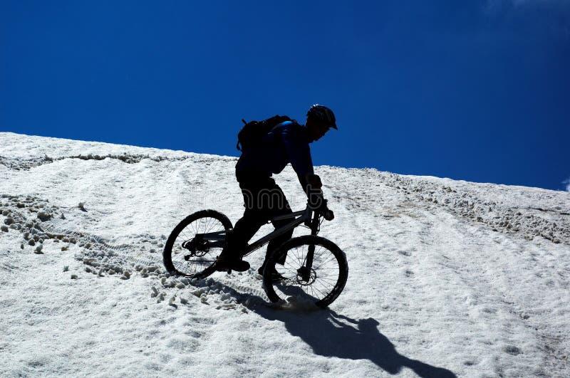 Motociclista del cielo, della neve e della montagna fotografie stock