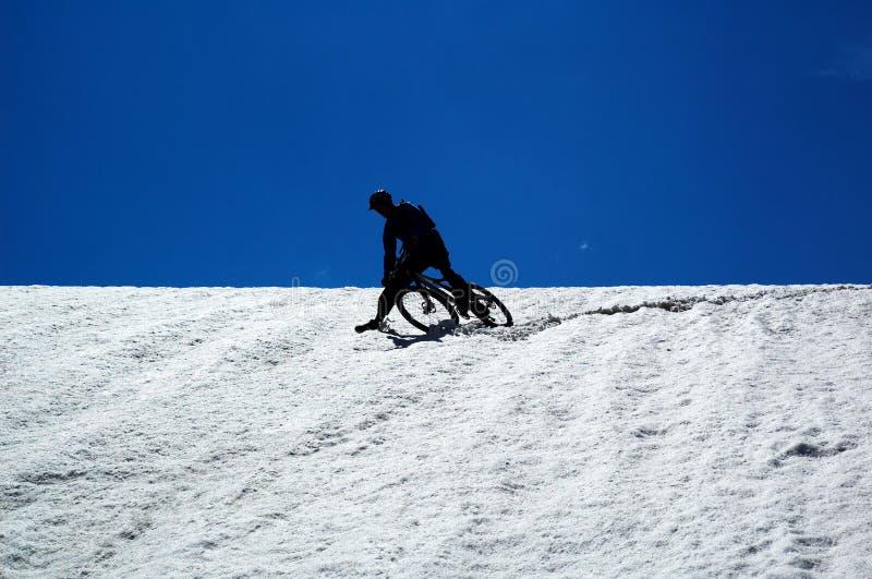 Motociclista del cielo, della neve e della montagna fotografie stock libere da diritti