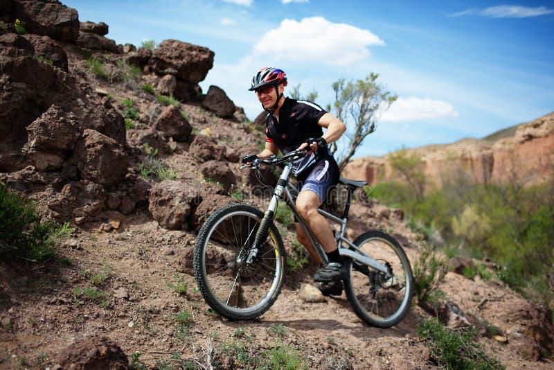 Motociclista della montagna in deserto selvaggio immagini stock