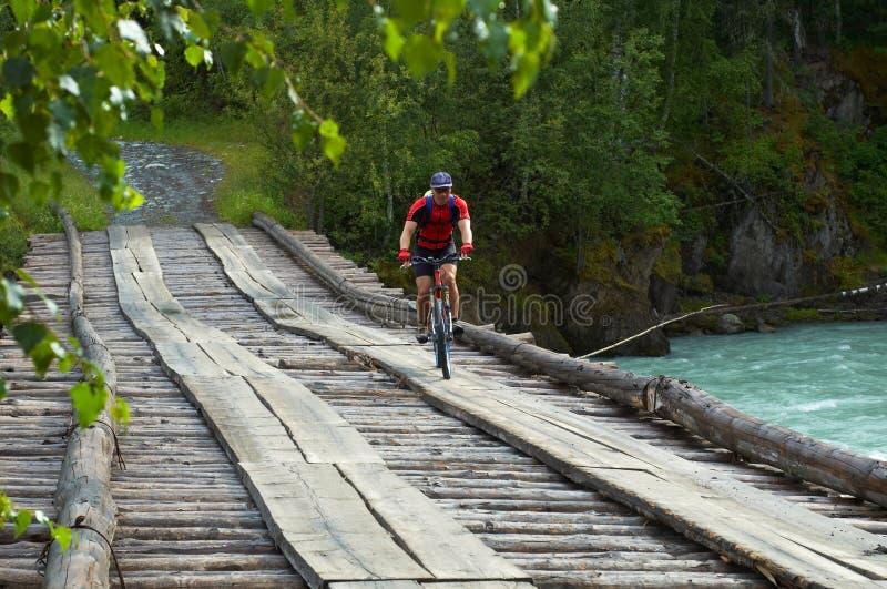 Motociclista della montagna sul vecchio ponticello di legno fotografia stock libera da diritti