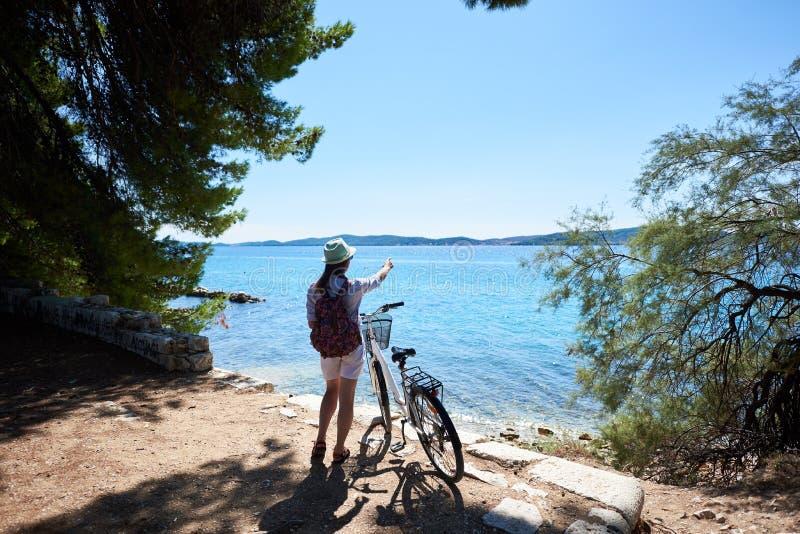 Motociclista do turista da jovem mulher com a bicicleta da cidade na cidade perto do mar imagem de stock