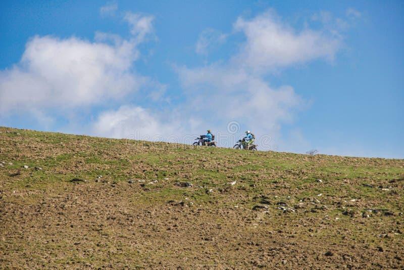 Motociclista dois no cume do monte contra um céu azul fotos de stock royalty free
