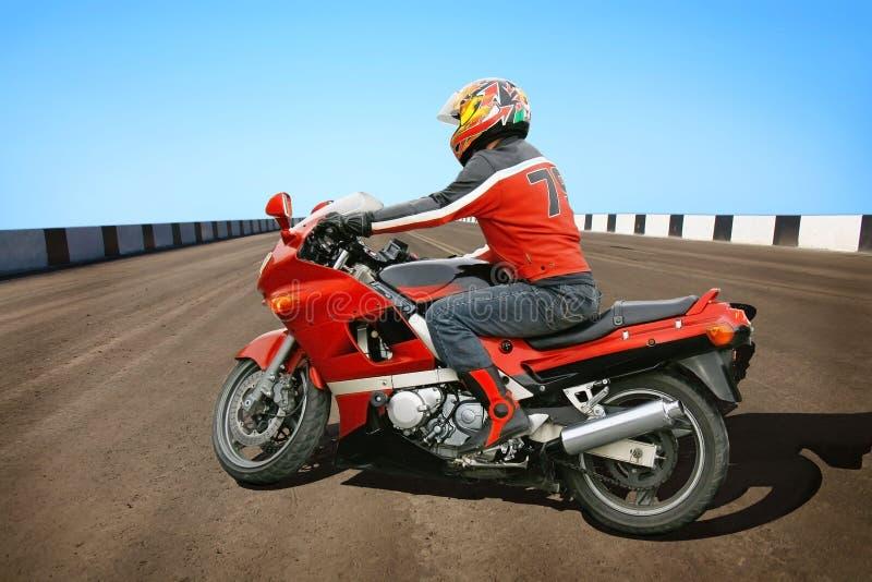 Motociclista e motocicleta vermelha imagem de stock