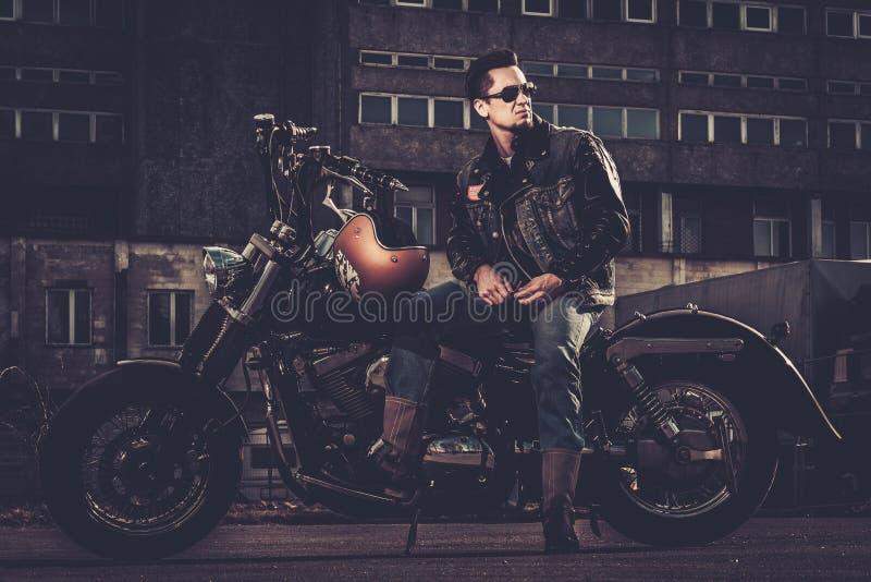 Motociclista e sua motocicleta do estilo do bobber fotografia de stock