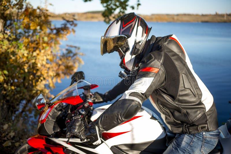 Motociclista em um capacete que senta-se em uma bicicleta dos esportes perto do lago foto de stock