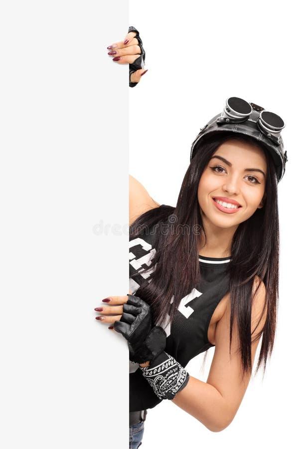 Motociclista femminile che sta dietro un'insegna in bianco fotografia stock