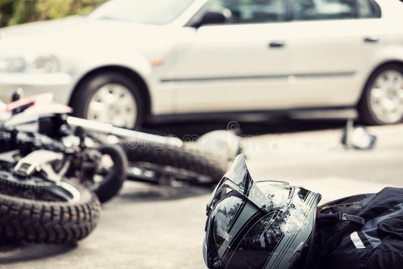 Motociclista inoperante na estrada após o incidente do tráfego com um carro imagens de stock