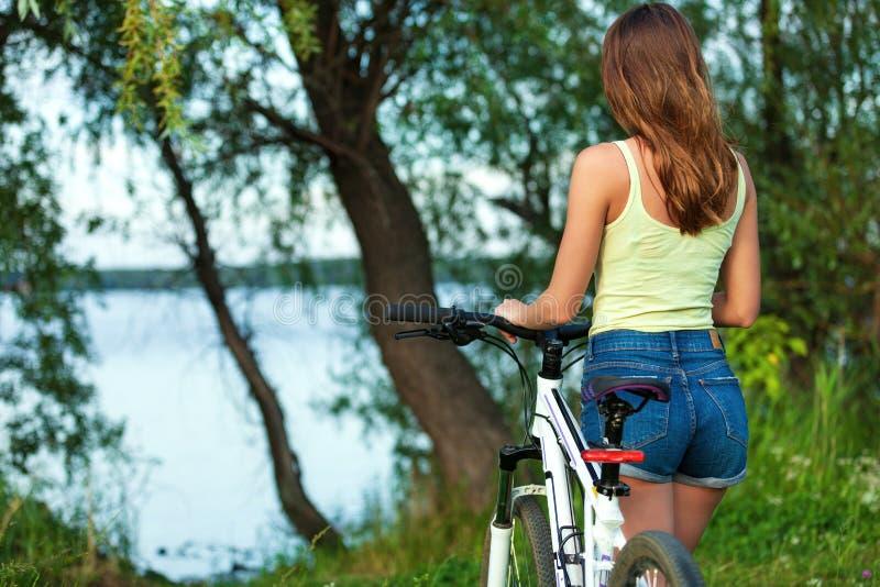 Motociclista magro da mulher com uma bicicleta em um parque ou em uma floresta foto de stock royalty free