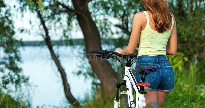 Motociclista magro da mulher com uma bicicleta em um parque ou em uma floresta fotografia de stock royalty free