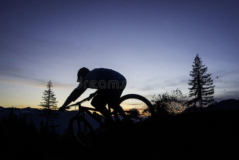 Motociclista mostrado em silhueta da montanha na ação imagens de stock royalty free