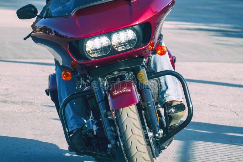 Motociclista nas calças de brim que montam uma motocicleta vermelha Front View fotos de stock royalty free