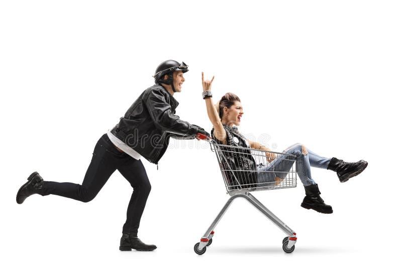 Motociclista que empurra um carrinho de compras com uma equitação punk da menina para dentro imagem de stock royalty free