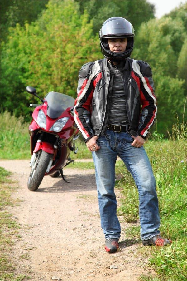 Motociclista que está na estrada secundária perto da bicicleta imagens de stock
