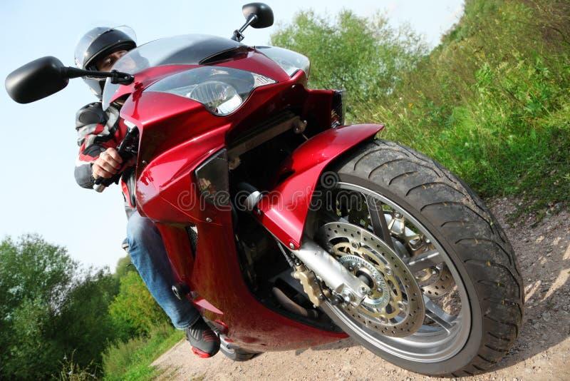 Motociclista que está na estrada secundária, vista inferior imagens de stock royalty free