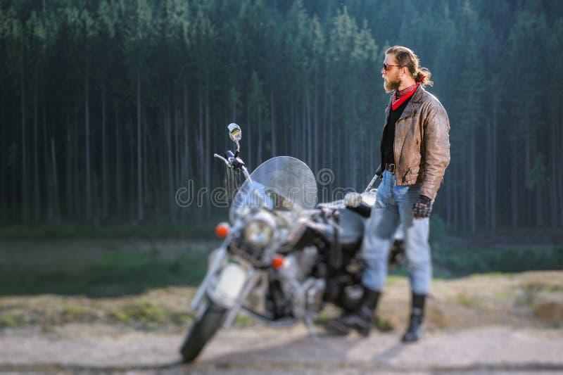 Motociclista que está por sua motocicleta feito-à-medida do cruzador fotos de stock royalty free