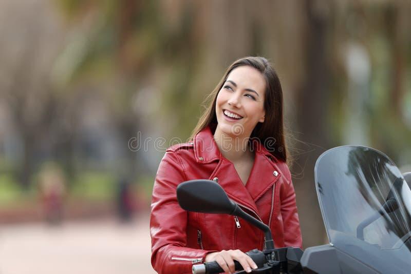 Motociclista que pensa olhando o lado em seu velomotor fotografia de stock royalty free