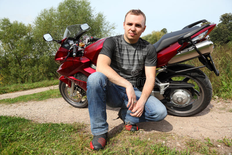 Motociclista que senta-se na estrada secundária perto da bicicleta imagens de stock royalty free