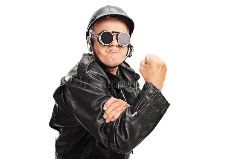 Motociclista senior impertinente che gesturing con il pugno afferrato fotografia stock