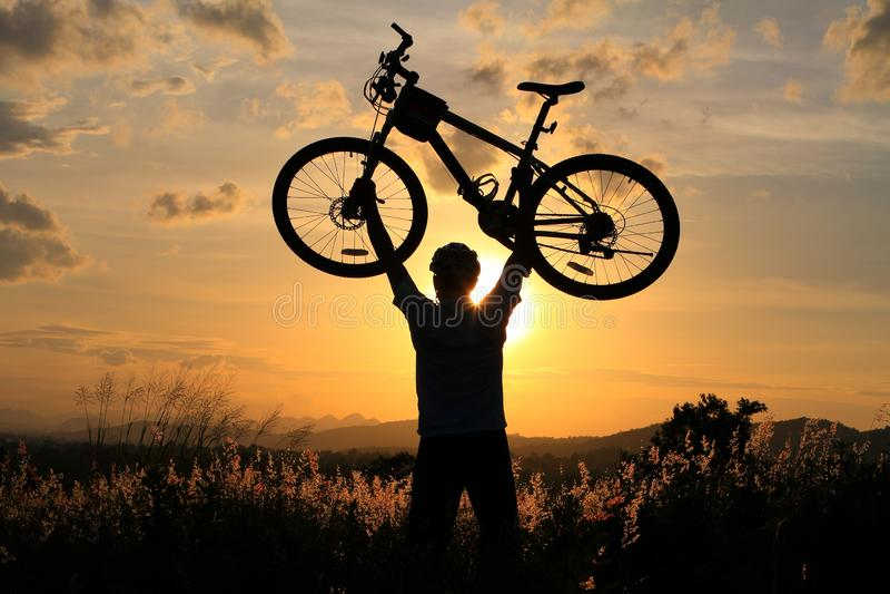 Motociclista sollevare la sua bicicletta dopo il giro lungo con la maratona nella regolazione della campagna fotografia stock