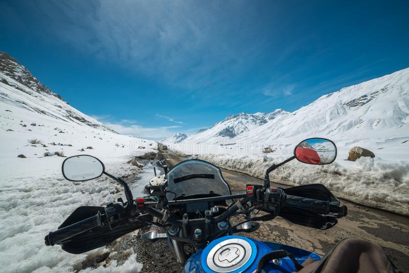 Motociclista in strada dell'Himalaya coperta da neve in India fotografie stock