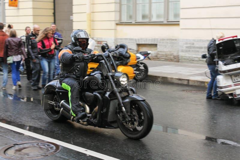 Motociclista su un motociclo nero immagini stock