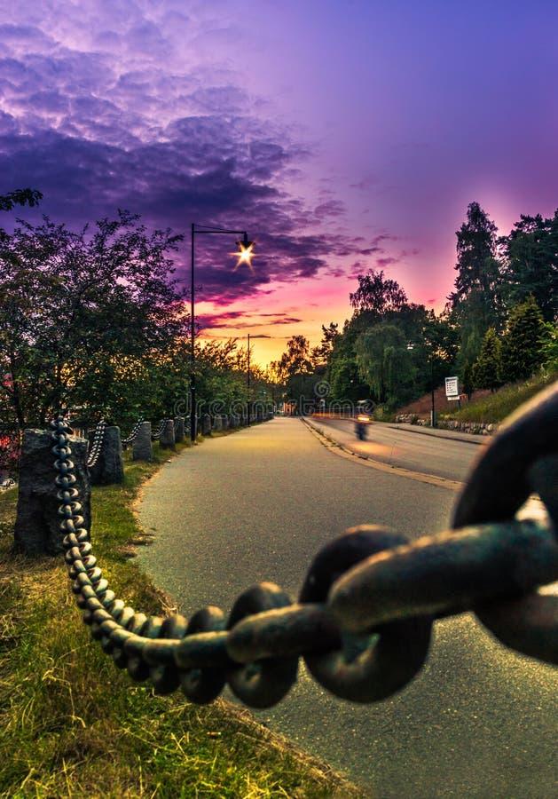 Motociclista su una strada di tramonto fotografia stock