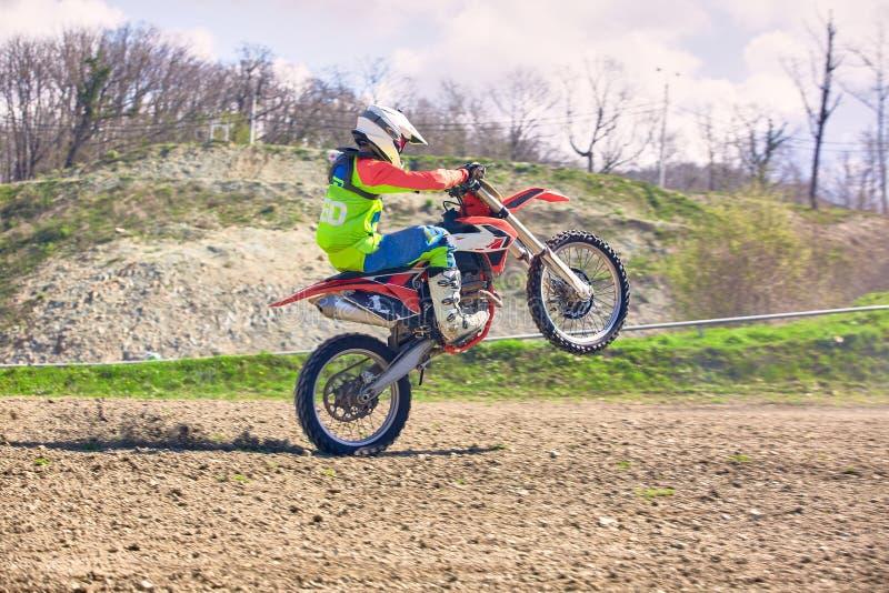 Motociclista sulle acrobazie del motociclo mentre guidando sulla vista laterale della ruota posteriore immagine stock libera da diritti