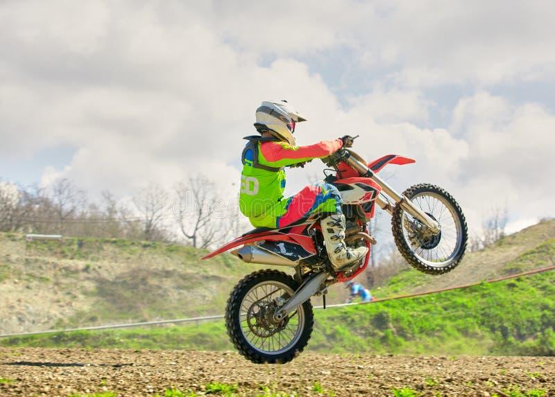 Motociclista sulle acrobazie del motociclo mentre guidando sulla vista laterale della ruota posteriore fotografie stock libere da diritti