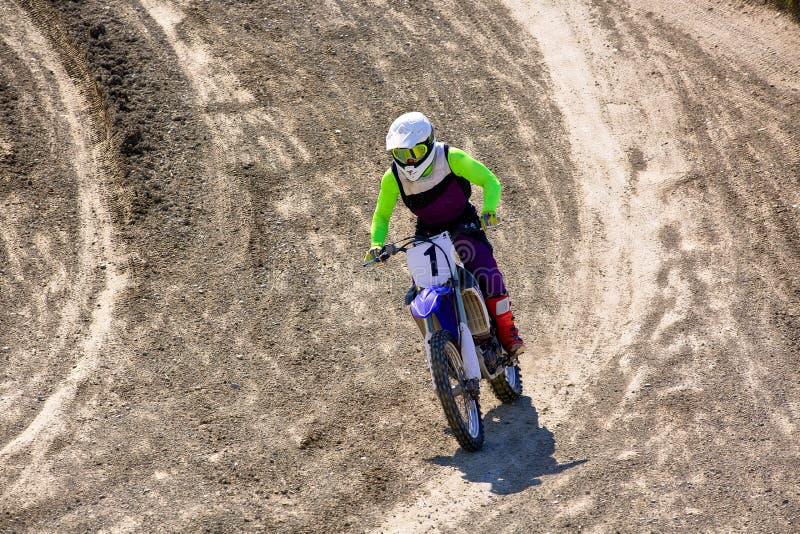 Motociclista sulle acrobazie del motociclo mentre guidando sulla vista laterale della ruota posteriore immagine stock