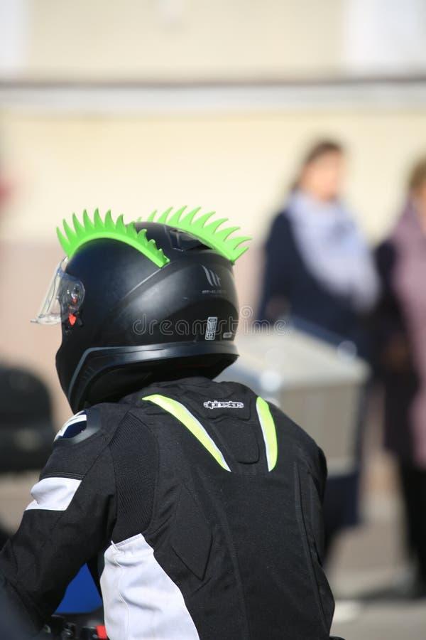 Motociclista in un casco con due creste verdi immagini stock libere da diritti