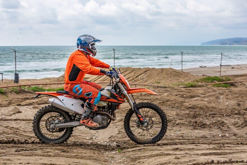 Motociclista in un vestito protettivo sulla motocicletta davanti al mare immagini stock